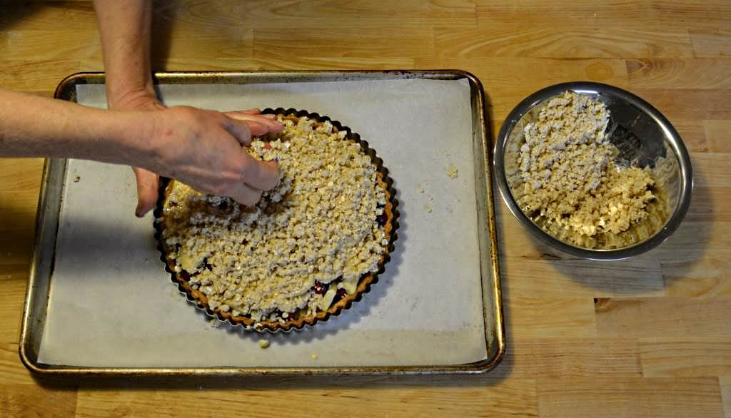 hand packing crumb topping on apple cranberry tart