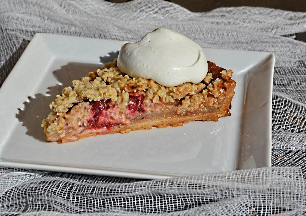 A plated slice of Mercedes Rick Apple Cranberry Crumble Tart with whipped cream awaiting the first bite